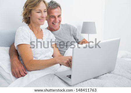 Smiling couple using their laptop together in bed at home in bedroom