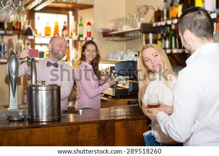 Smiling couple waiting for table in restaurant and drinking wine at tavern. Focus on the woman - stock photo