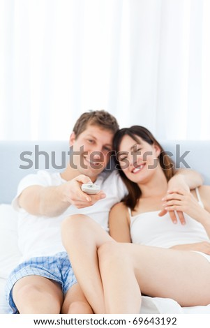 Smiling couple watching tv at home - stock photo