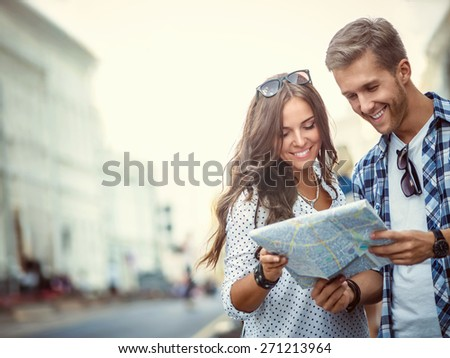 Smiling couple with a map outdoors - stock photo