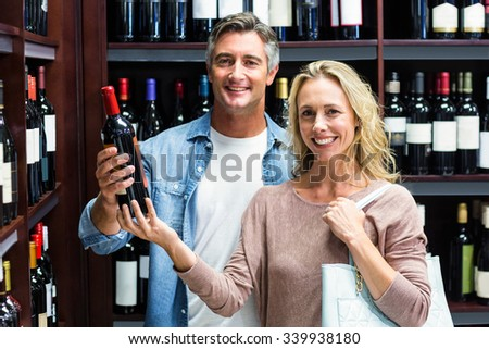 Smiling couple with bottle of wine in supermarket - stock photo