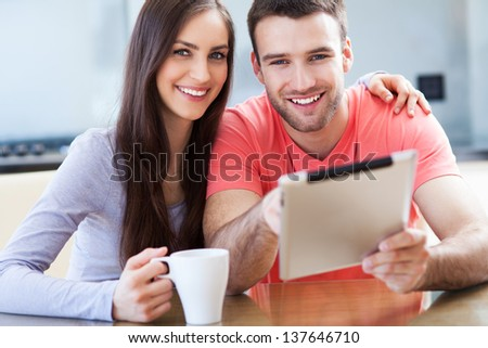 Smiling couple with digital tablet - stock photo