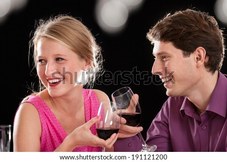 Smiling couple with glasses of red delicious wine - stock photo