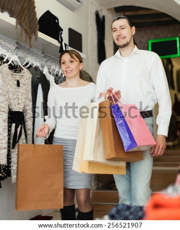 smiling couple with shopping bags at clothing shop