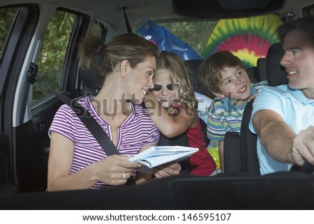 Smiling couple with two happy children in the car