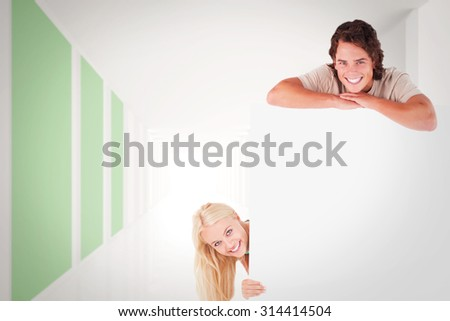 Smiling couple with whiteboard against modern white and green room with window - stock photo