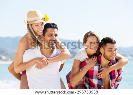 smiling couples hugging on beach enjoying romance and sun. Focus on the left couple - stock photo