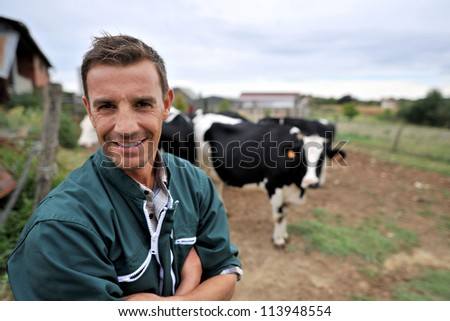 Smiling cow breeder standing in in front of cow herd - stock photo