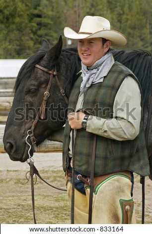 Smiling cowboy holding the head of his horse - stock photo