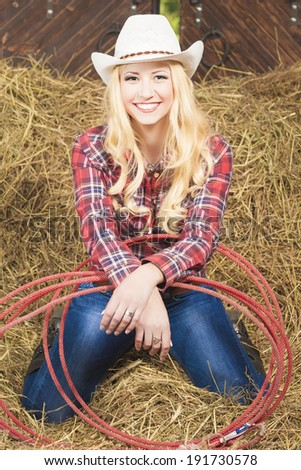 Smiling Cowgirl With Lasso Rope in Cattleshed. Vertical Image - stock photo