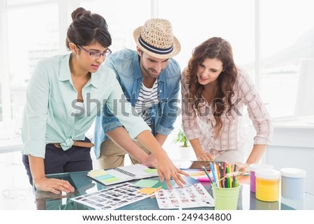 Smiling coworkers editing photos together in the office - stock photo
