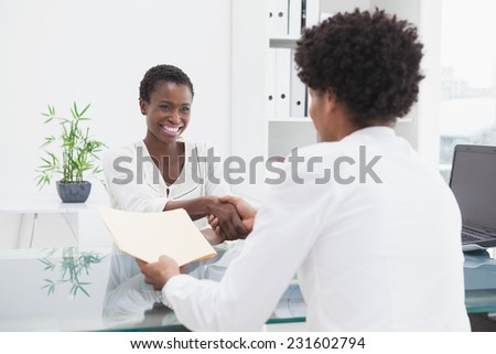 Smiling coworkers sitting and shaking hands in the office - stock photo