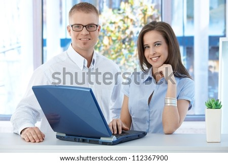 Smiling coworkers standing in office, using laptop computer, looking at camera.