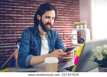 Smiling creative businessman using mobile phone in office - stock photo