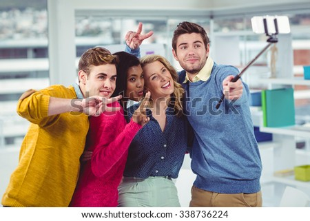 Smiling creative team posing for a selfie in casual office - stock photo