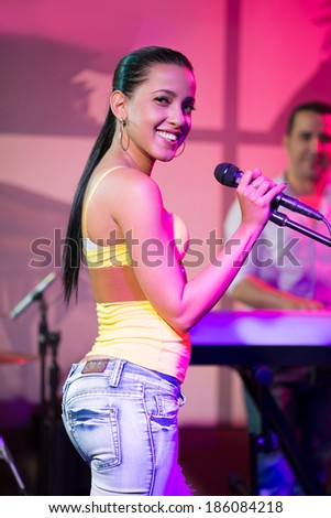 Smiling Cuban woman standing with the microphone - stock photo