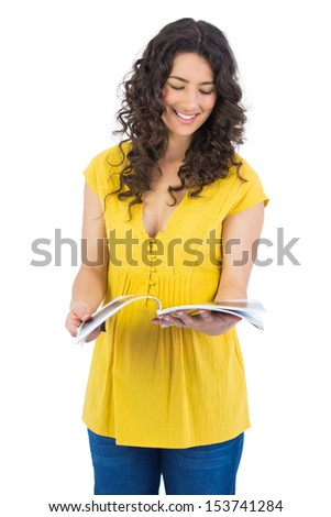Smiling curly haired brunette reading magazine on white background - stock photo