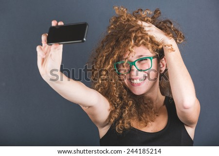 Smiling Curly Woman Taking Selfie - stock photo