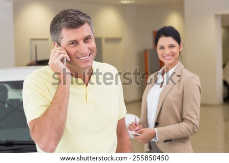 Smiling customer calling with his mobile phone at new car showroom