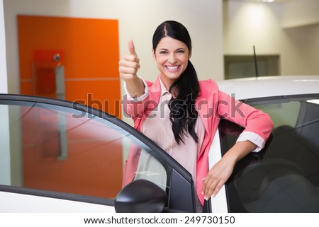 Smiling customer leaning on car while giving thumbs up at new car showroom - stock photo