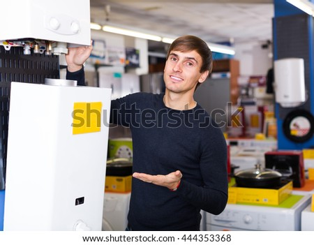 Smiling  customer looking at domestic boilers in hypermarket
