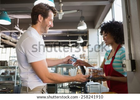 Smiling customer paying by credit card at the bakery - stock photo