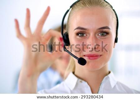 Smiling customer service girl showing ok, isolated on white background. - stock photo