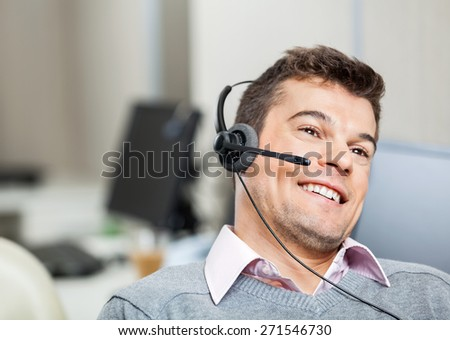 Smiling customer service representative wearing headset while looking away in office - stock photo