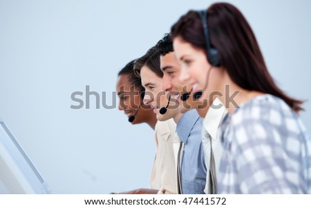 Smiling customer service representatives working in a call center