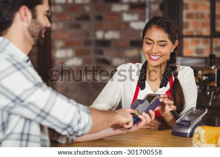 Smiling customer typing on the pin terminal at the coffee shop - stock photo