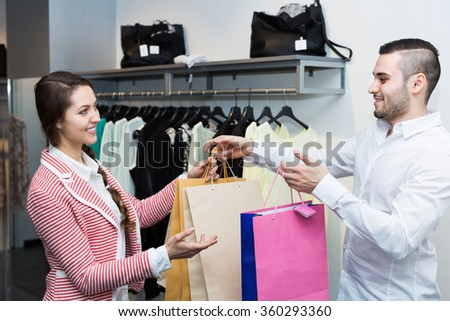 Smiling customer with cheerful shop assistant at boutique
