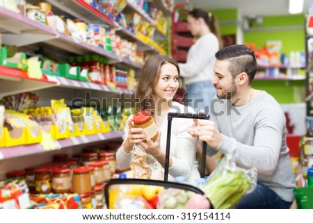 smiling customers standing near shelves with canned goods at shop