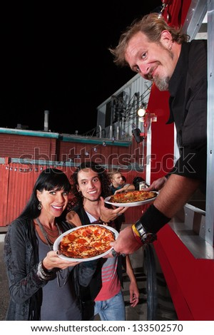 Smiling customers with food truck owner and pepperoni pizza