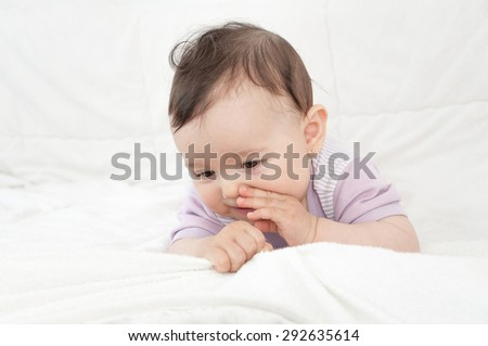 Smiling cute baby girl lying on stomach in bed. High key  - stock photo