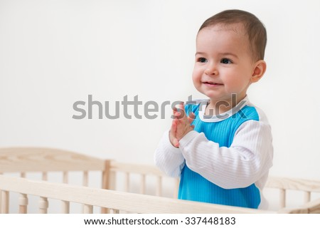 Smiling cute  baby toddler look at one side in the bed on white background