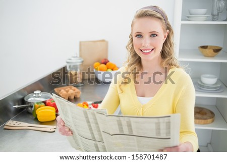 Smiling cute blonde holding newspaper in bright kitchen