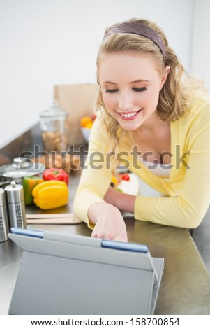 Smiling cute blonde looking at tablet in bright kitchen - stock photo