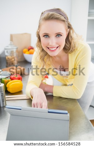 Smiling cute blonde using tablet in bright kitchen - stock photo