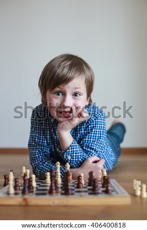 smiling cute boy playing chess   - stock photo