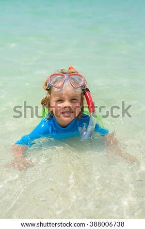 Smiling cute boy wearing snorkeling mask ready to dive in the sea - stock photo