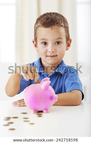 Smiling cute boy with coins and piggy bank - stock photo