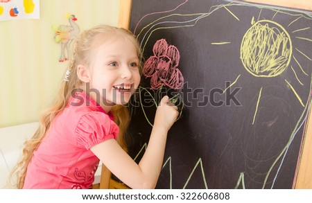 Smiling cute girl drawing on blackboard