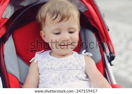 smiling cute girl sitting in red stroller