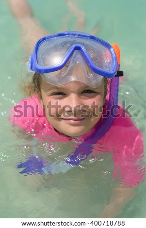 Smiling cute girl wearing snorkeling mask ready to dive in the sea - stock photo