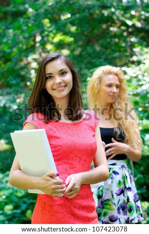 Smiling cute girl with a book with another girl on the background - stock photo