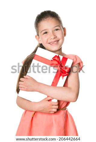 Smiling cute girl 8-9 years holding in hands birthday present in festive package. Isolated on a white background. - stock photo
