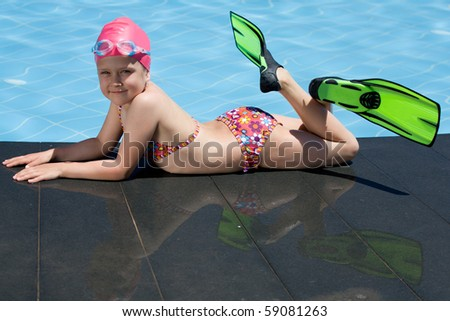 Smiling cute little child in bathing cap, glasses and fins is lying on the swimming pool ledge - stock photo