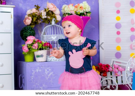 Smiling cute little girl among flowers  - stock photo