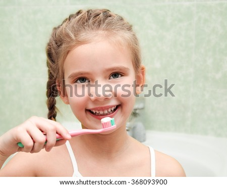 Smiling cute little girl brushing teeth in bathroom hygiene concept