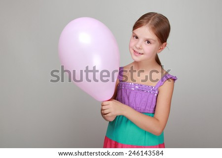 smiling cute little girl in a bright sundress holding balloon - stock photo